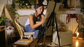 Il giovane artista femminile sta parlando con qualcuno nello studio stock footage
