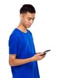 Il giovane asiatico ha letto il messaggio sul cellulare Fotografia Stock
