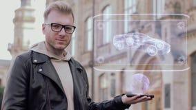 Il giovane astuto con i vetri mostra ad un ologramma concettuale la vettura da corsa moderna video d archivio