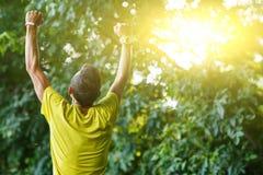 Il giovane atleta è indietro con le sue mani su in parco Fotografia Stock Libera da Diritti