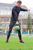 Il giovane atleta attraente dell'uomo fa l'addestramento di forza con i pesi a Immagine Stock