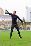 Il giovane atleta attraente dell'uomo fa l'addestramento di forza con i pesi a Fotografie Stock Libere da Diritti