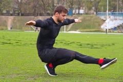 Il giovane atleta attraente dell'uomo fa l'edificio occupato su una gamba allo stadiu Fotografia Stock Libera da Diritti
