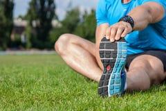 Il giovane atleta in buona salute sta scaldandosi in stadio Fotografia Stock Libera da Diritti