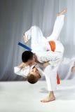 Il giovane atleta con una cinghia arancio esegue il nage-waza di tecnica Immagine Stock