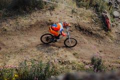 Il giovane atleta del cavaliere sulla bicicletta guida su una traccia di montagna fotografia stock