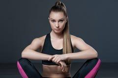 Il giovane atleta femminile attraente sta avendo un resto fotografia stock libera da diritti