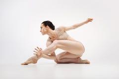 Il giovane atleta muscolare che allunga nel bianco ha colorato lo studio Fotografia Stock Libera da Diritti