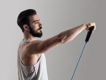 Il giovane atleta nell'allenamento della canottiera sportiva con la banda elastica della resistenza che fa la spalla si esercita Immagini Stock