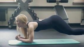 Il giovane atleta rende ad esercizi una plancia con rotazione nella palestra Donna attraente stock footage