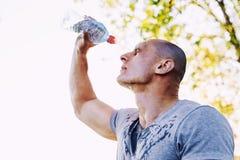 Il giovane atleta sta rinfrescandosi con acqua, lo sport e lo stile di vita sano fotografie stock libere da diritti