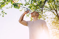 Il giovane atleta sta rinfrescandosi con acqua, lo sport e lo stile di vita sano Immagine Stock