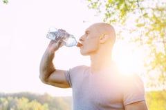 Il giovane atleta sta rinfrescandosi con acqua, lo sport e lo stile di vita sano Fotografia Stock