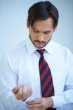 Il giovane attraente che fa sulla sua camicia cuffs Fotografie Stock