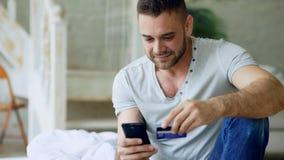 Il giovane attraente con lo smartphone e l'acquisto della carta di credito su Internet si siedono sul letto a casa fotografia stock