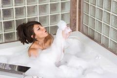 Il giovane attraente gorges la donna che cattura il bagno di bolla Fotografia Stock