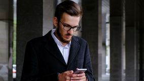 Il giovane attraente in un vestito classico ed i vetri, stanti nel distretto aziendale, fa un acquisto di Internet video d archivio