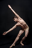 Il giovane ballerino flessibile che allunga nello scuro ha acceso lo studio Fotografia Stock