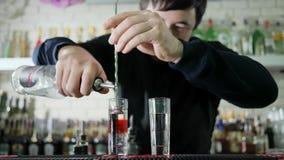Il giovane barista che fa il cocktail colorato e versa scozzese luminoso dalla bottiglia in vetro con l'alcool sullo scrittorio s archivi video
