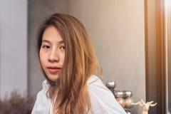 Il giovane barista femminile asiatico che si rilassa sedendosi nella sua propria caffetteria ed è riscaldato dal sole caldo dentr Immagini Stock