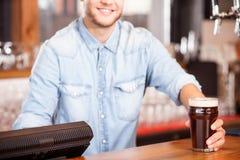Il giovane barista maschio allegro sta servendo il cliente Immagini Stock