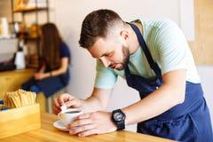 Il giovane barista maschio prepara il caffè fotografia stock libera da diritti