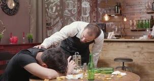 Il giovane barista prova a svegliare un cliente ubriaco stock footage