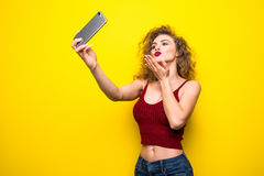 Il giovane beautifulgirl con un'acconciatura riccia invia il bacio del selfie La ragazza di risata prende il selfie dal telefono  Fotografia Stock