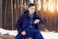 Il giovane bello, alla moda ed in rivestimento esamina il suo orologi Molla in anticipo, giorno soleggiato Modo del ` s degli uom Fotografia Stock Libera da Diritti