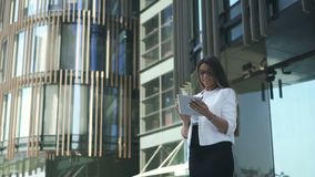Il giovane bello avvocato della donna sta utilizzando la compressa, stante sul fondo dell'edificio per uffici stock footage