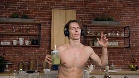 Il giovane bello con il torso nudo del torso è musica d'ascolto in cuffie sta bevendo la bevanda fresca con le verdure e archivi video
