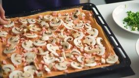 Il giovane bello cuoco della donna ha messo i funghi sulla pasta della pizza nella cucina a casa stock footage