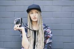 Il giovane bello fotografo della donna sta tenendo la macchina fotografica Fotografia Stock