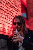 il giovane bello in occhiali da sole e nel bere del bomber porta via il cocktail dalla tazza di plastica nell'ambito di luce ross immagini stock