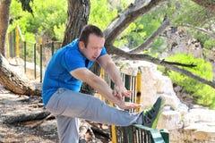 Il giovane bello sta facendo allungando gli esercizi in abiti sportivi d'uso dello sportivo della foresta in natura del paesaggio Fotografie Stock Libere da Diritti