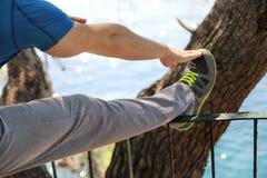 Il giovane bello sta facendo allungando gli esercizi in abiti sportivi d'uso dello sportivo della foresta in natura del paesaggio Immagine Stock