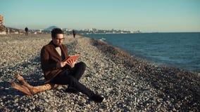 Il giovane bello sta riposando su un litorale nella sera con la compressa video d archivio