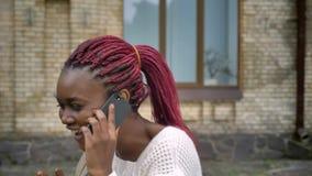 Il giovane bello studente africano che va a partire dall'università e che parla sul telefono, donna con il rosa teme camminare ne stock footage