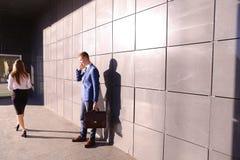 Il giovane bello, uomo d'affari che parla sul telefono passa dal beaut Fotografie Stock Libere da Diritti