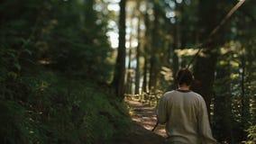Il giovane bello in vestiti tradizionali cammina da solo nel bello in anticipo della foresta carpatica verde pittoresca video d archivio