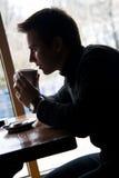 Il giovane beve il caffè in un ristorante Immagine Stock Libera da Diritti
