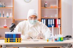 Il giovane biochimico che indossa vestito protettivo che lavora in laboratorio fotografia stock libera da diritti