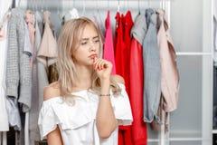 Il giovane blogger grazioso della ragazza sta con un'espressione premurosa sul suo fronte sui precedenti dei vestiti che appendon immagini stock
