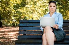 Il giovane businessgirl sexy funziona con il suo computer portatile sul banco Fotografie Stock Libere da Diritti