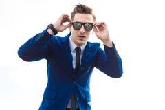 Il giovane busunessman attraente in vestito blu e gli occhiali da sole stanno la o Fotografie Stock