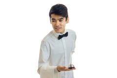 Il giovane cameriere affascinante che tiene una Bell e pende in avanti Fotografia Stock