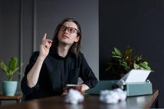 Il giovane in camicia nera, con capelli lunghi, alzati il suo dito sulla manifestazione ha un ideea, messo ad una tavola vicino a immagine stock