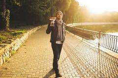 Il giovane cammina dalla chitarra della tenuta e del lago Immagini Stock