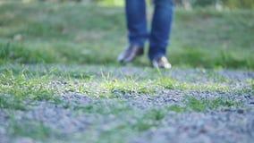 Il giovane cammina giù la via Primo piano delle gambe in jeans ed in stivali video d archivio