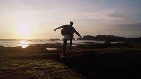 Il giovane cammina lungo la spiaggia, salti, apre le sue armi ampie contro il bello tramonto Movimento lento video d archivio